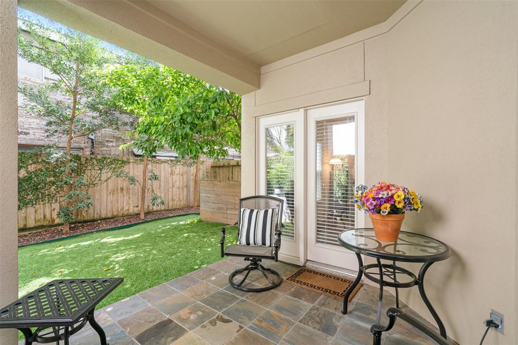 The covered patio is a quiet space to enjoy the lush greenery in the back yard.