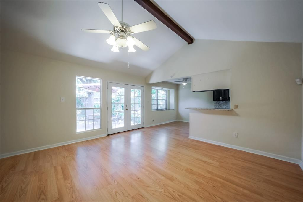 View towards the back door and kitchen. Wood laminate flooring makes this room shine.