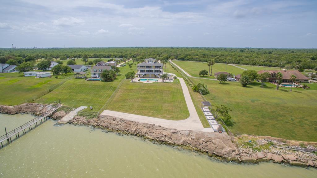 NO FLOODING! 2.8 ACRES ON TRINITY BAY - 160  OF WATERFRONT, STUNNING WRAPAROUND BALCONIES, POOL, OUTDOOR KITCHEN, POOLBATH, FIREPIT, WHOLE HOUSE GENERATOR, 3 CAR GAR. QUALITY OF CONSTRUCTION IS 2ND TO NONE - ENGINEERED BLDG W/ 56 BELL BOTTOM PIERS, CONCRETE WALLS ON GROUND LEVEL. INTERIOR FEATURES ISLAND KITCHEN & OPEN DEN, GAMEROOM, 5 BR/4 BATH, GYM, 4TH FLR STUDY W/ PRIVATE BALCONY & ENDLESS VIEWS. EXCEPTIONALLY WELL MAINTAINED. SIMPLY TOO MUCH TO LIST. YOU WON T BE DISAPPOINTED.