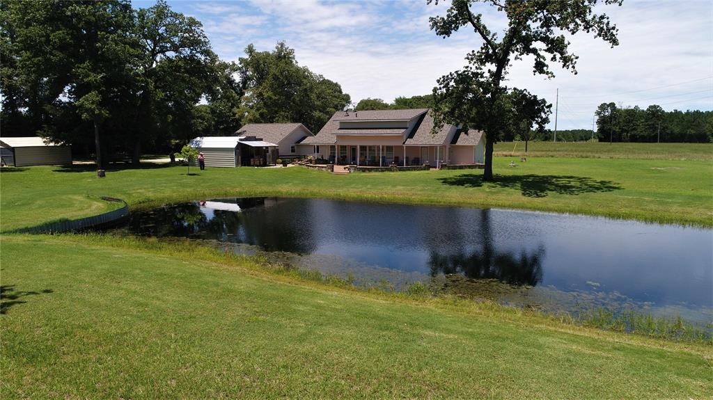 This gorgeous custom home is situated on 26.602 pristine acres.The large living area has a nice built-in entertainment center and the hickory hardwood hand scraped floors throughout the living, kitchen, and dining area are to die for! The island kitchen is has granite counter-tops, tons of custom cabinets, and stainless appliances for the cook in the family. The master suite offers built-ins, huge walk-in closet, and a large bath with walk-in shower and large soaking tub. Upstairs, you will be impressed with Oak flooring staircase, as well as the open balcony that leads to a large bedroom, a loft complete with an aspen wood ceiling that could be used as a third bedroom or office, and a full bath. There is a large garage complete with a kitchenette and a full bathroom. Outdoors, you will fall in love with the 1,400 sq. ft. scored concrete patio complete with a fire-pit overlooking the fishing pond. There is an outdoor kitchen/cook shack, as well as 2 storage buildings. Call us today!