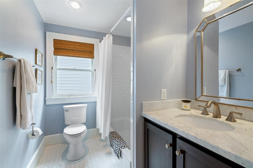 The upstairs secondary bathroom is located just off the two upstairs secondary bedrooms. It includes gorgeous subway tile shower surround and a marble vanity.