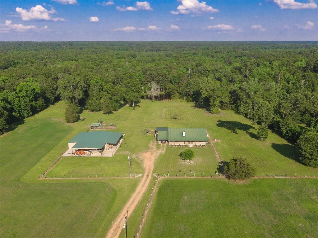 You've got to see this! This 3 bedroom cedar sided home sits in the center of an unrestricted 17 acre tract. The property features a stocked pond, and seeded/fertilized bahia, jiggs, and bermuda grass hay pastures, producing 230-270 bales each cutting and 4-5 cuttings a season! The 3 bedroom home features a vaulted ceiling living room, master suite, and amazing back yard entertainment spot complete with an inground pool and covered eating area and hangout. If that's not enough the huge 48x57 metal shop with electricity and plumbing should do it! In addition to the metal shop with 2 12' and 1 8' roll up doors and a walk through door, there is also a 42x24 covered and slabbed overhang with 220/240 volt service for your RV or living quarter trailer hookups. There is also a 48x15 overhang also slabbed for other outdoor equipment. This amazing property has it all and more, don't miss out on this amazing opportunity to own a private and secluded high and dry oasis in Coldspring ISD.