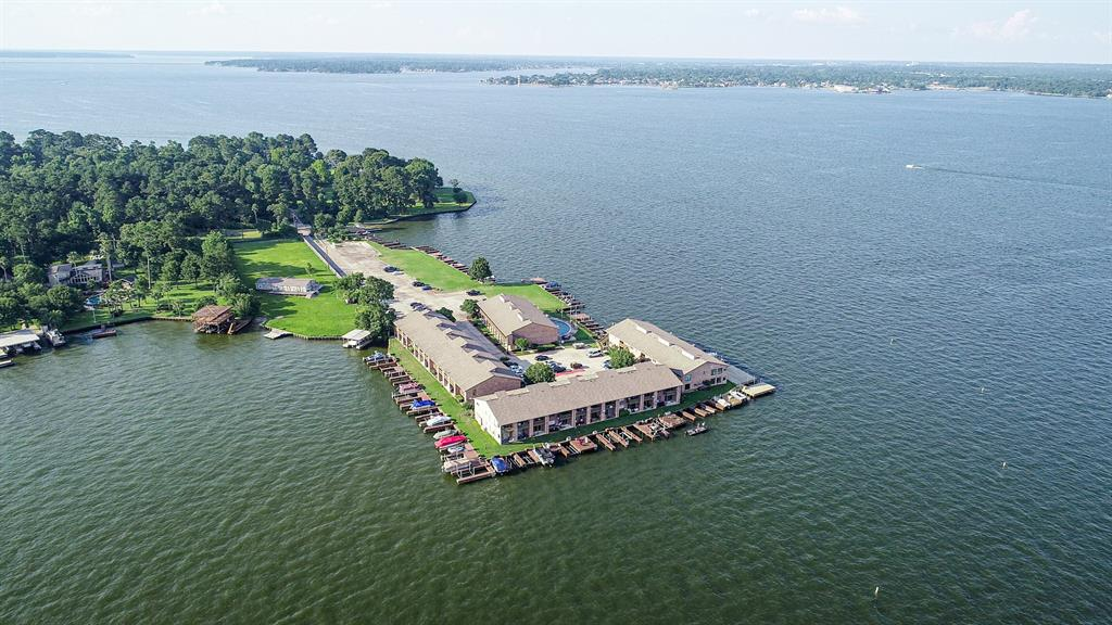 FEEL LIKE YOU ARE ON VACATION EVERY DAY!!! Best waterfront condos on Lake Conroe for the money - hands down! You get million dollar water views, 2 boat slips with lifts, and a picturesque setting that is so quiet and peaceful. You can be on your boat, from your own boat slips, and on the lake in minutes. When you aren't on the lake enjoy beautiful views from this second story unit overlooking open water. This complex is well maintained and still has the lowest condo fees around. There is a beautiful pool overlooking wide open Lake Conroe water, and the complex is gated as well. I also love that there is a lot of green space to play on if you wish, or walk your dog, etc. Inside is just what you need for a weekend at the lake! Two beds, two baths, and living and kitchen. These units DO have an washer and dryer in them, and this unit can come fully furnished including washer, dryer, and fridge. You'll love these condos and you can't beat the price. Come get it quick...