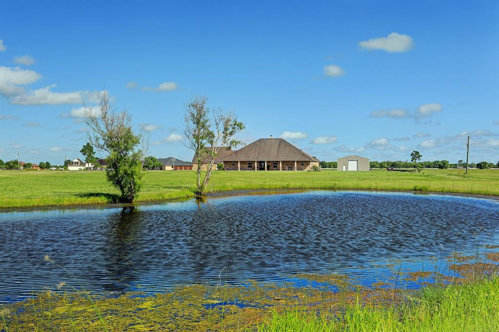 Gorgeous 3 bedroom 3.5 bath custom home in Savannah Plantation on 10.5 acres w/ two ponds. Solar powered gated entrance welcomes you. Home features large country porch & beautiful entry into a formal dining & study w/french doors. Family room w/wood burning fireplace, wood look tile flooring, custom built ins, high ceilings & access to patio.Gourmet kitchen w/granite, lots of cabinet & counter space, kitchen island w/bar & stainless steel appliances.Mud room or breakfast room off the kitchen.Master suite w/access to back yard & en suite w/ double sinks, separate shower, garden tub & huge custom walk-in closet!2 spacious secondary bedrooms share jack & jill bathroom w/their own vanities & storage. Home has 500 gallon propane tank & on demand water heater for house & garage! Backyard features 30,000 gallon pool w/hot tub & stone waterfall. Full bath for pool guests on back of garage. Garage apartment has full bath & open concept. 40'x60' barn for equipment storage. Located in Alvin ISD!!
