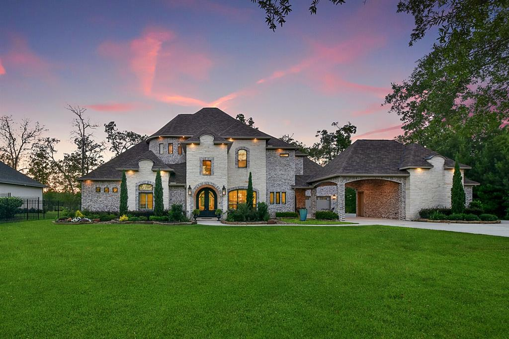 Stunning custom home situated on a one acre waterfront lot with beautiful mature oak trees. Over 5,600 square feet of luxury living with gorgeous designer finishes & custom touches throughout. Custom double iron front doors open to the two story foyer with sweeping staircase. The kitchen is a chef's dream with high-end stainless steel Wolf appliances including double ovens & a 6 burner gas cooktop, large island & walk-in pantry with tons of built-in storage. The kitchen opens to the family room that has great lake views. Walk-in wine room enclosed by wrought iron door. Luxurious master retreat features a coffee bar, freestanding tub & dual marble vanities. Huge media room with theater style lighting & 9.2.2 Atmos surround sound. Extensive built-ins, Plantation shutters, hardwood flooring, designer lighting & more found throughout the home. Covered outdoor living areas on both the 1st & 2nd levels - the main level has a beautiful outdoor stone fireplace.