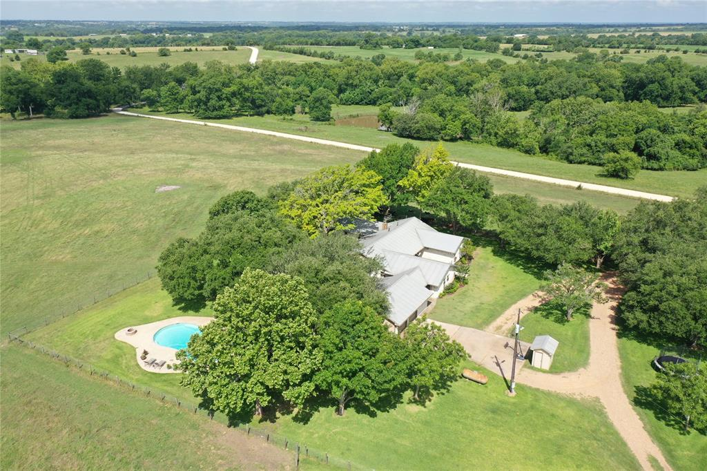 Here's the place, the place you've been searching for months to find. The approximate 105 rolling acres with a beautifully updated, move-in ready house, that's privately placed high away from everyone. The property offers improved pastures planted in jiggs and high quality grasses, strong perimeter and cross fencing, a stocked pond, 66'x50' utility barn with concrete floors, electricity, and water, and another barn with stalls and metal pens. A  completely remodeled, efficient, 3500 sf house sits, surrounded by mature Oaks providing shade as you gaze and admire the long view. A 2-car garage, attached with a breezeway, gives access to an office and extra storage. The backyard setting includes a new swimming pool/hot tub, along with a fire pit and a constant breeze to enjoy the evening sunsets. This exquisite property has over 4300' of road frontage, and borders Mill Branch, a habitat for wildlife.  The Davoody Ranch has it all, and once you see it, you'll want to put your name on it.