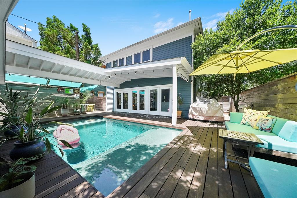 This backyard is an abundant oasis. The sparkling and heated pool has double seated ledges. French doors fill the back of the house, and seating areas surround the pool.