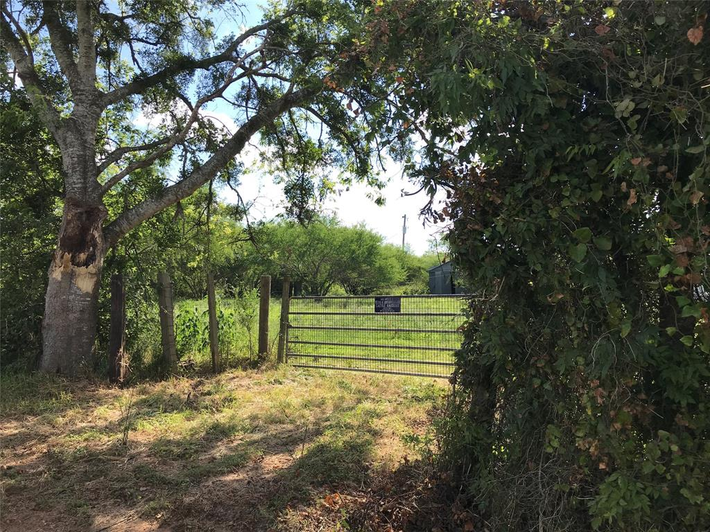 This 50.091 acres tract is being sold out of a 95.14 acre tract. UNRESTRICTED & AG EXEMPT.  Improvements include two barns and an older 1984 mobile home.  The smaller barn is  870 sq ft; the other consists of 4000 sq ft; built in 2004.  In addition,  the seller will convey the Mahindra tractor, trailer and other implements including the front and loader, mower and scrapper.  Barb wire fencing; gate.