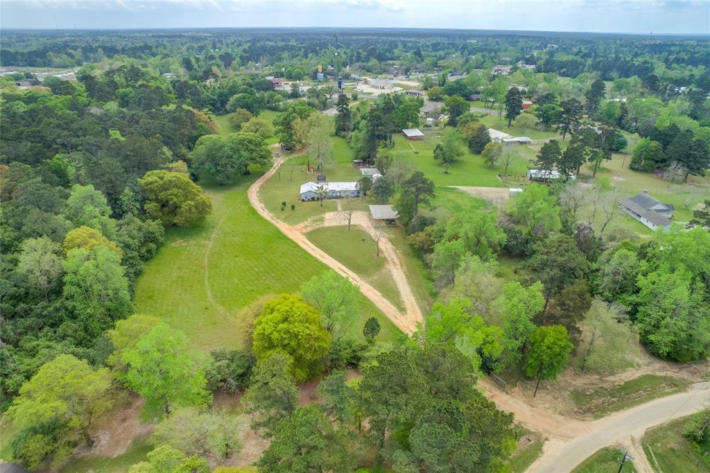 This is a great opportunity to purchase 8 unrestricted acres in the town of Coldspring, walking distance to Junior High school and be in this quaint little town in 2 minutes. The property is beautiful with rolling terrain, pecan and walnut trees, deer roaming through the pastures, chicken pen with coop and 2 outbuildings just to list a few of the features. The home is a ranch style home with 3 bedrooms and 2 baths. The master bedroom is huge with separate on suite bath that was updated a year ago.The Master Suite addition to home was done in 1996 and Metal Roof was added in 2015.  Large carport with room for boat and vehicles. The back deck is a great large space , with covered area, that is perfect for sitting in the morning with coffee or in the evening with friends and family watching the kids play or just enjoying the quiet and watching the deer.  Be at the lake in 10 minutes or IAH in Houston within an hour.  Schedule your showing today to view this great property before its gone.