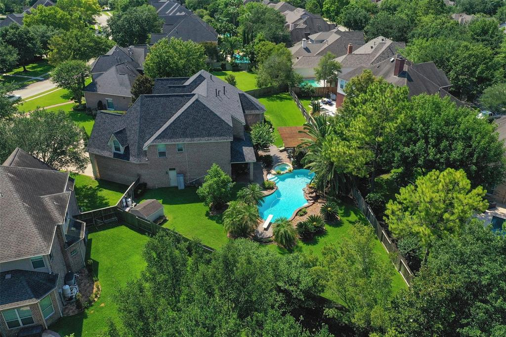 Stunning Tommy Baily custom home in the heart of Cinco Ranch located in gated Bayou Oaks. You will love the huge back yard complete with pool, spa, covered seating, outdoor kitchen and firepit! You will note the Texas flair throughout the home as you enter through the tall entry door complete with leaded glass Texas star! As you enter the soaring two story entrance you will take in the beautiful formal living and dining rooms as well as the grand, sweeping staircase with wrought iron balusters. The gourmet kitchen- with built in refrigerator,  Thermador cook top and custom cabinetry-is open to the family room complete with limestone hearth and mantel. The master bedroom and bath offer a luxurious retreat for the owner. There are 3 to 4 bedrooms on the second level along with a game room and study nook.  Lots of separate spaces for at home working or school! Extensive storage and closet space throughout this gorgeous home. Live inside 99 and enjoy life in award winning Cinco Ranch!