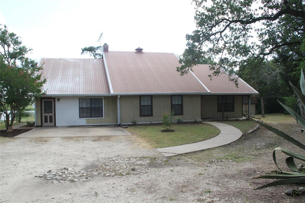 Looking for quiet, country property less than 5 miles from Giddings.  This property includes a 3 bedroom/3 bath home w/ a converted garage for extra living space.  Vinyl plank & laminate flooring recently installed (June 2020) and most of the interior was freshly painted.  Outbuildings include 30'x40' shop w/ 2 overhead doors & covered side storage for trailer, tractor, etc & there's also a storage shed w/ lead to covering for more storage. Come check out the view while enjoying the large covered back porch.