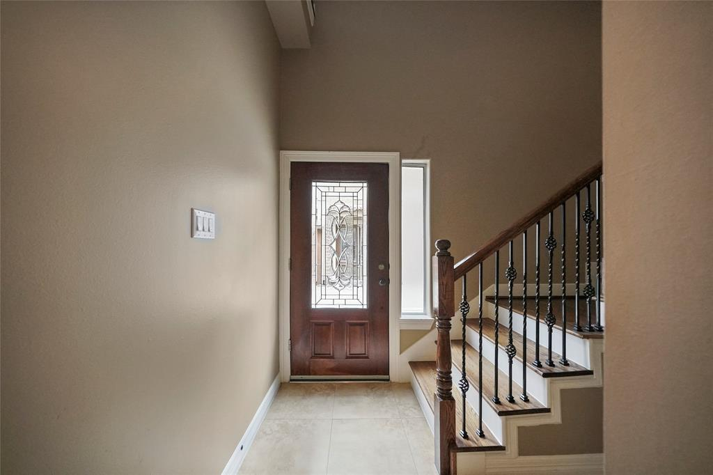 Receive your guests in this formal entryway. The staircase includes iron balusters, painted white risers, and hardwood steps.