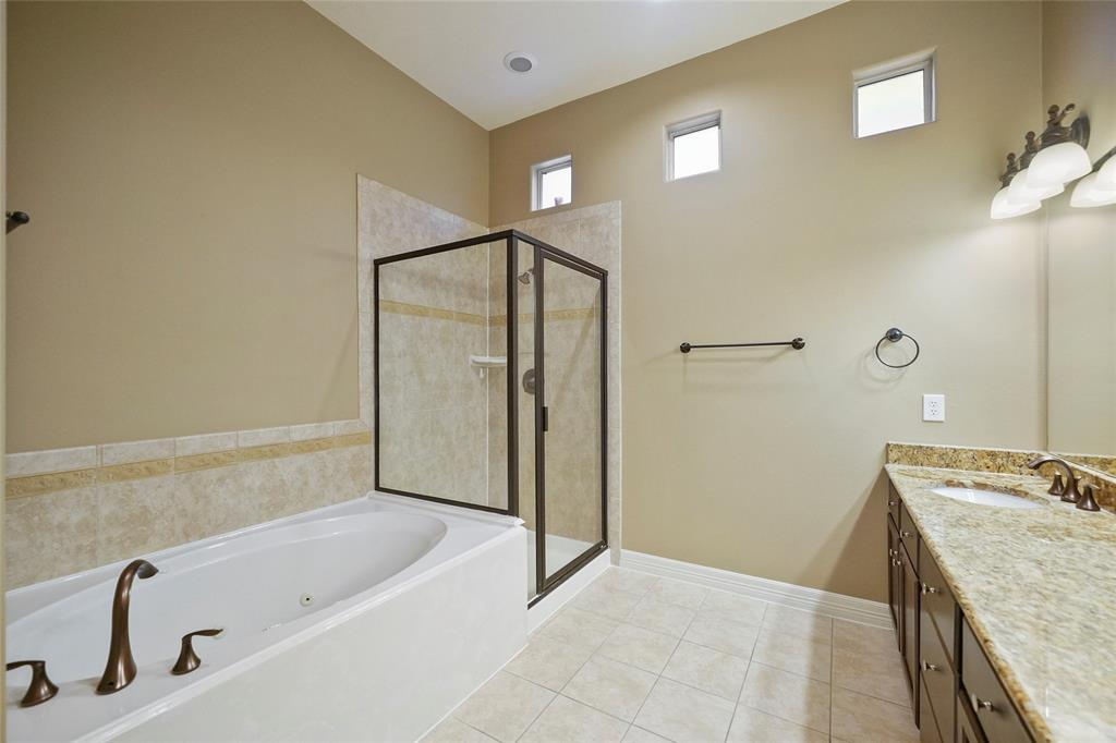 The master bathroom includes a stand-up shower and jetted tub. It also includes some great natural light. The vanity includes some great storage and granite countertops.