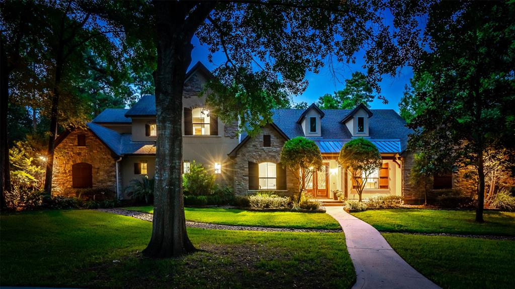 Where else could you find a beautiful custom home on five acres of lushly forested and landscaped grounds, just five minutes from The Woodlands and I 45? Drive up the gated drive that circles a lovely pond to the double door entry and behold the quality of the inside featuring extensive travertine flooring, flowing through the private study, living area and kitchen. The media/game room are combined off the kitchen. The primary suite has wood flooring and has a lush bath with a large closet. The primary BR looks out to the lush backyard and pool. There is a large laundry room and second bedroom and bath down plus a powder room. The kitchen is a cook's delight with double islands and lovely granite counters with bar seating and dining area. Upstairs has all wood flooring with two bedrooms and a shared bath. The outside is so private with a large outdoor kitchen, fireplace, grill and a lovely pool/spa. Large three car garage and out building for extra storage.