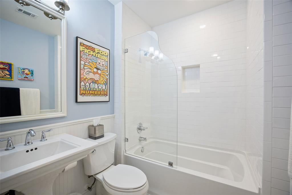 The guest bathroom is located just off both secondary bedrooms. It includes a gorgeous subway tile surround, wainscoting, and linen closet.