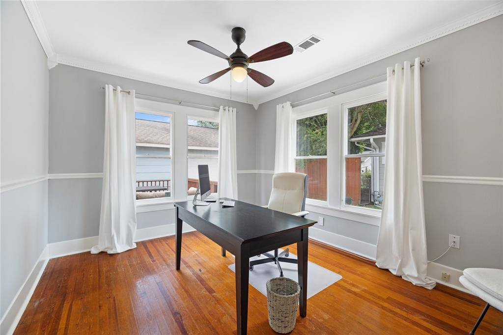 Currently being utilized as an office, this downstairs bedroom offers plenty of space for a guest bedroom. It includes hardwood floors and classic millwork.