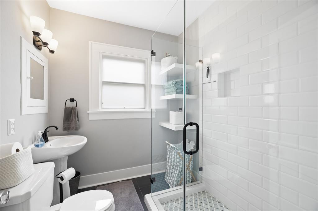 Downstairs bathroom has been gorgeously renovated. It is located just off the secondary bedrooms.