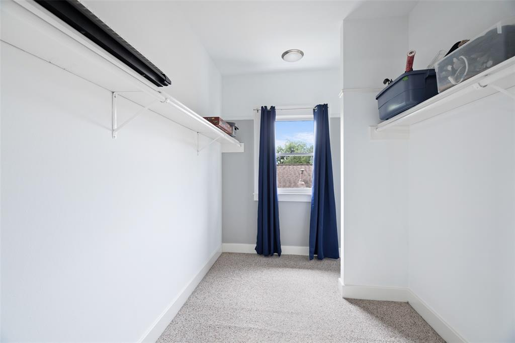 This large walk-in closet is located off the primary bedroom upstairs.