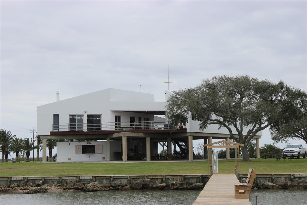 This gorgeous furnished home setting on 2.12 acres over looks the Carancahua Bay with a 240' bulk head that sleeps 22 people. Perfect for entertaining family and quests. Complete with tile floors, exotic counter tops, slide outs in cabinets for easy access. 2 living areas both with wood burning fireplaces, lots of storage. Beautiful concrete patio to enjoy the sunsets. Property has a 6' X 240' lighted pier, with boat stalls/lifts, green fishing lights. Property has 3 septic systems, 2 water wells, 3 central A/C units, home also sets on concrete platform and pillars. Windows in main house and bedrooms have electric shutters. 2000' decking and walk ways! Grapefruit, Orange, Olive and Fig trees to enjoy! Be sure to check the video on you tube link https://youtu.be/hFQqdtp7Vsg.