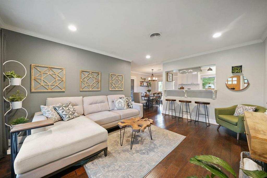 The beautiful living room features gorgeous wood floors and crown molding.