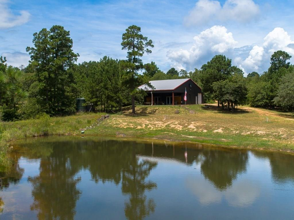 Modern steel frame home + tiny home! ~ Nestled in 53+ acres of pine & oak forest, overlooking a scenic pond.  Escape from the city, experience the peace & quiet of country life & star-gazing while still being minutes from Austin, ABIA & Lockhart. Barndominium w/ kitchen, Murphy bed in living area plus one bedroom with queen bunks & full bath with shower. Think 'West Elm' in the pines! Furnishings available. Expansive porch with great views. Ample storage area. Tiny home has Airbnb history. Gated entry.