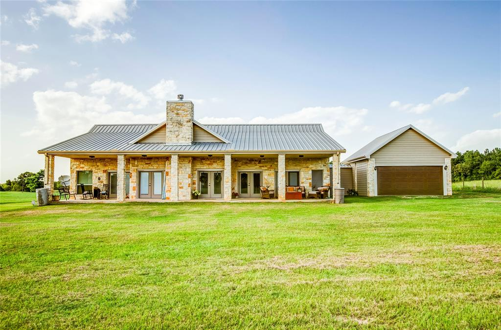 Country living at its best-Custom built brick home on 29+ acres. Large open living space with doors opening out to porch all across the front of the home. Kitchen designed to delight the cook,family and guests, as room for all with easy move around design, just relax at the bar when you are lucky enough just to get to observe and give the cook advice. A welcoming Master BR with large WIC, bath with separate tub, open design shower, light and bright. Split Guest BR provides privacy and yet location assures you're a part of the family. Spacious Utility Room opens to walkway that leads to the attached garage with overhead doors on front and back for ease in getting vehicles where you need them. At north end of the property you'll find living quarters with kitchen, bath and plenty of space for family member or guests to feel welcome and be comfortable. There's an attached large barn/shop with room for any farm projects you might have, plus additional covered bay parking for tractors, ATVs.
