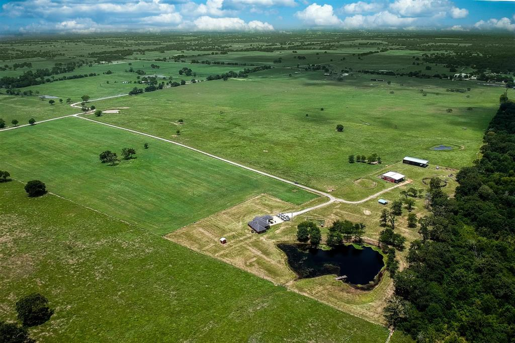Exceptional 66.71 acre horse ranch set up for raising and working the best in breeds.  Property includes large barn with tack room, pens, lockable storage and extra storage on second level, hay shed, open round pen, RV hook-up pad, cross fenced pastures with 3 separate tanks positioned in each pasture.  Ranch style house situated next to the stocked fishing pond, fishing pier and clustered shade trees.  Home has a large centrally located kitchen over looking family room w/ fireplace and views of pond, extended patio for grilling and outside entertaining/living, master suite separate from other bedrooms for privacy, all rooms very nice sizes, formal den/dining or office space large utility with pantry storage and plumbed for extra bath, attached garage and extended concrete parking.  Fences in great shape, hay pastures ready for 2nd cut and possible 3rd cut coming again this year (crop part of sale).  So much to see/learn about this property.  Schedule in advanced for personal viewing.