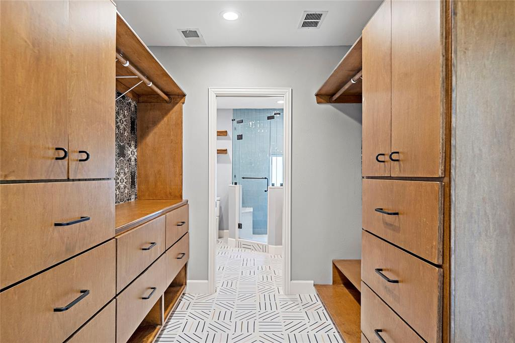 Space between primary and en suite serves as the closet with custom, high-end storage cabinets.