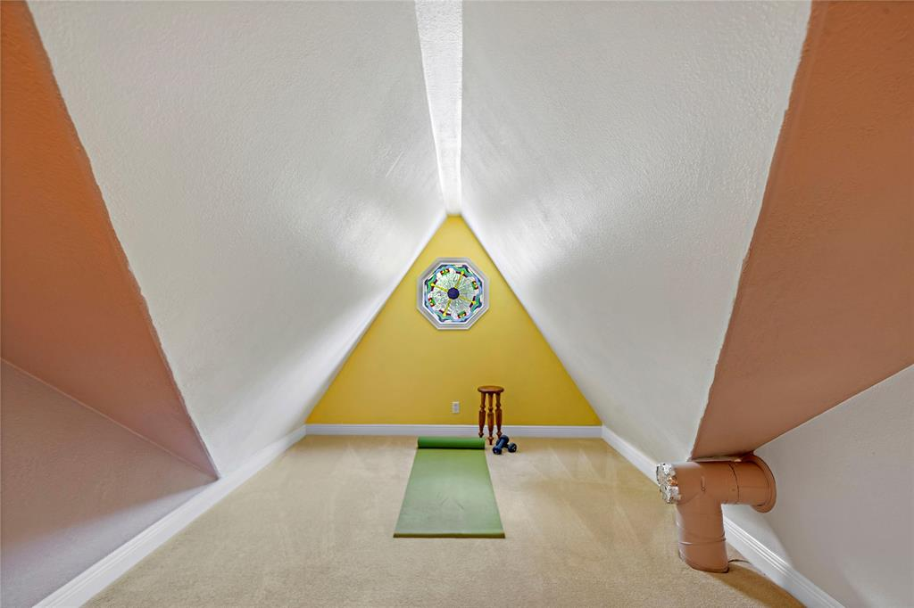A lofted space with stained glass window sits above the primary bedroom and is the perfect spot to create your own private exercise, yoga, or hobby studio.