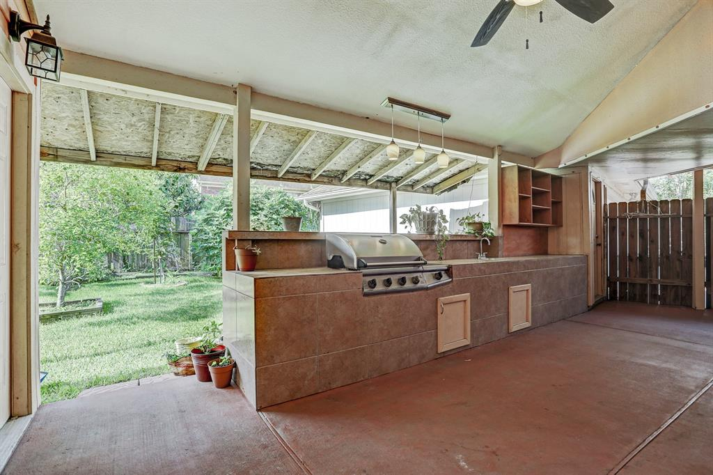 Outdoor kitchen with sink and gas grill.