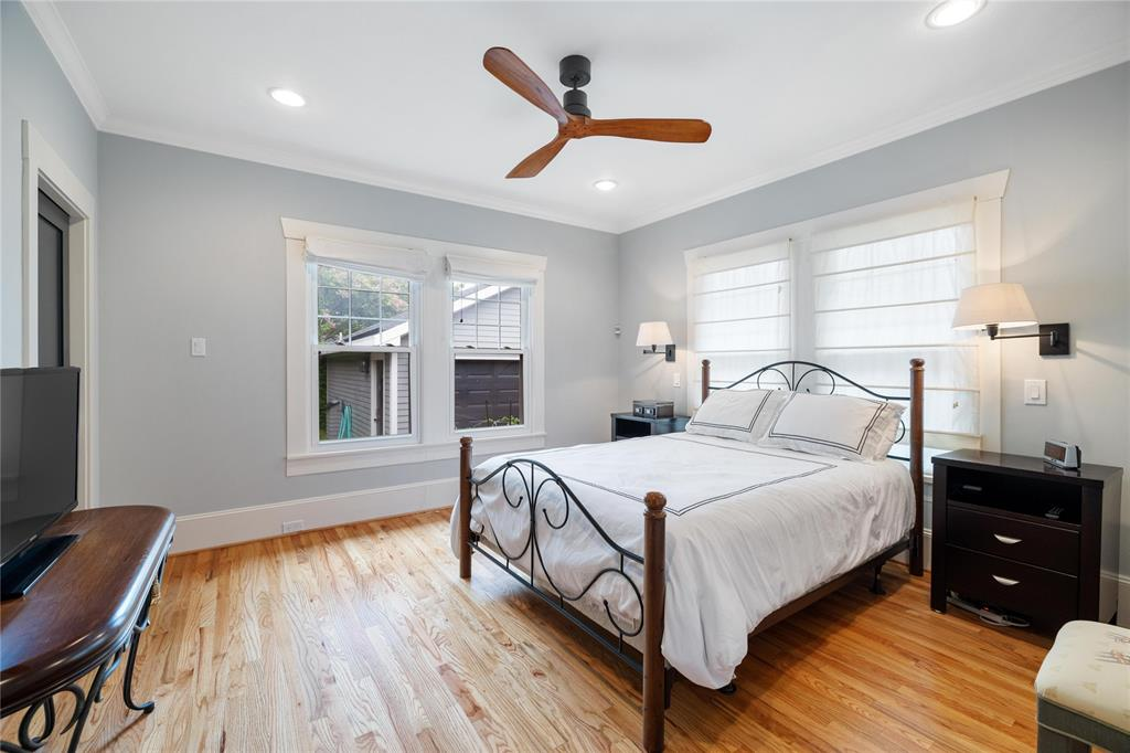 The beautiful wood floors continue into the primary bedroom that features a large walk-in closet and recessed lights.
