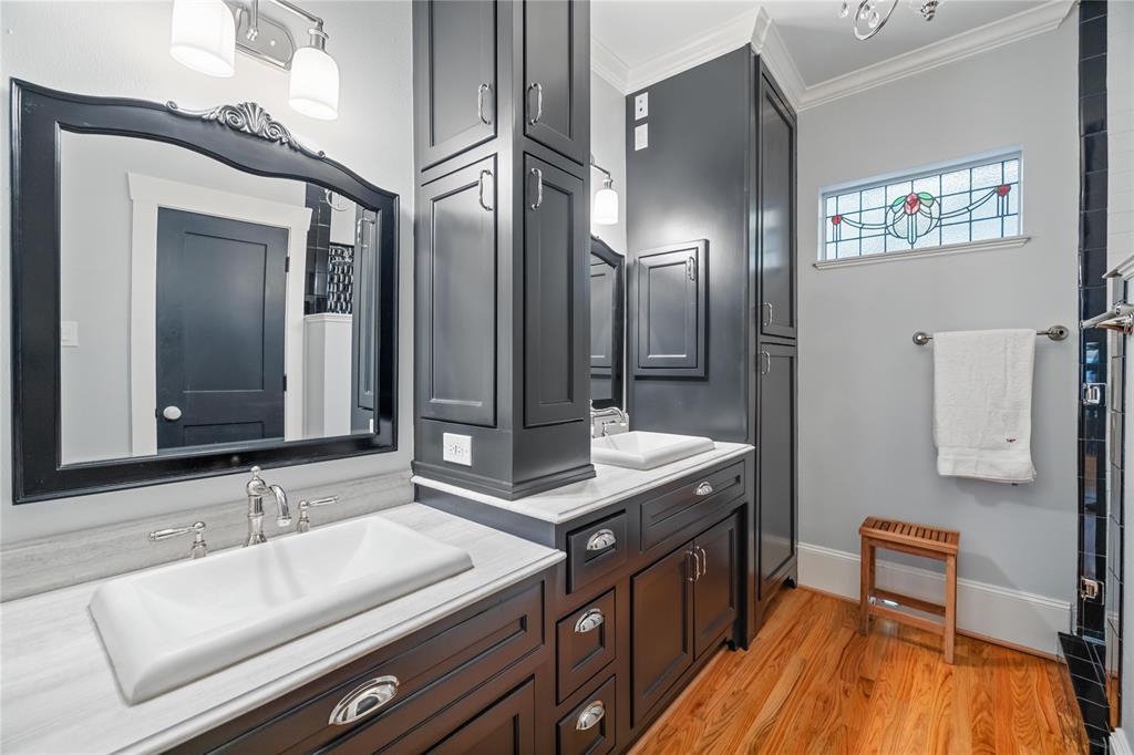 The luxurious bathroom features dual vanities and a chandelier light fixture.