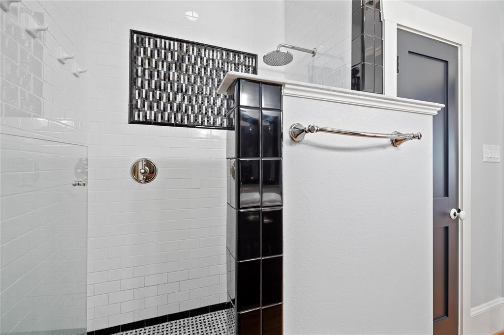 The spacious shower features a multi-jet system and rainfall shower head.