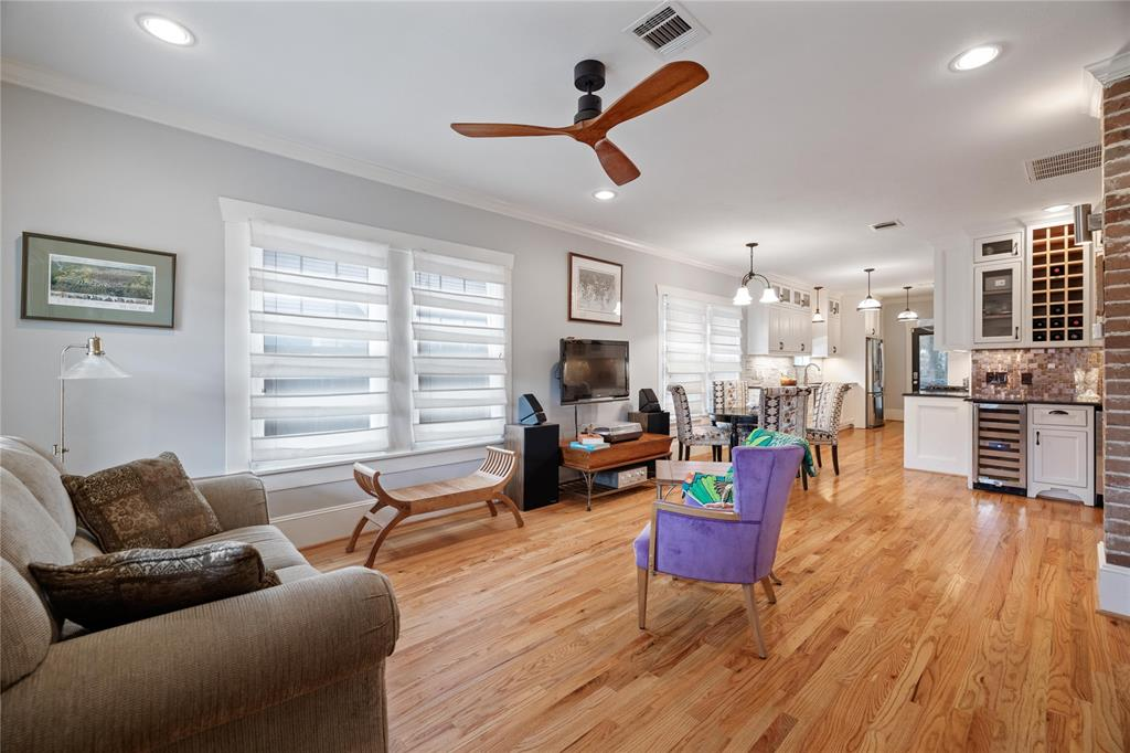 The spacious open floor plan features wood floors, crown molding, and lots of natural light.