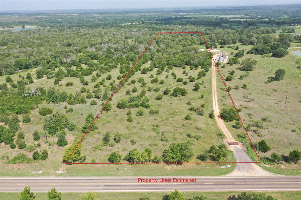 10.76 Acres in Lee County between Giddings and Dime Box. Partially open with scattered mesquite, oaks and cedars, and partially wooded with a deep gully near the back of the property. Bluebonnet Electric overhead powerlines cross through the tract and Lee Co. Water Supply meter at the front. Existing entrance with cattle guard and gravel road into the property. Ag. valuation in place for extremely low taxes, by cattle grazing. Property dimensions are 270.78' (front) x 1746.85' (south) x 268.92' (back) x 1676.53' (north boundary). Property is fenced on 3 sides, as fence along the southern boundary is taken down so cattle can graze continuously with the neighboring property. There is no fence along the boundary where the oil well pad sits on the adjacent property.