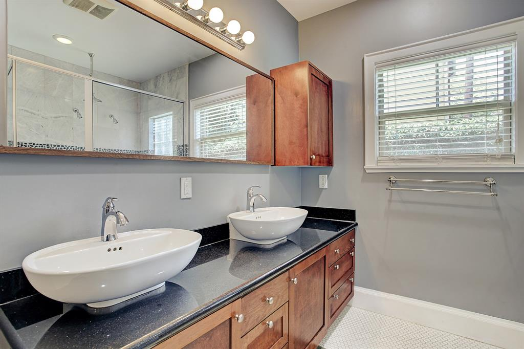 The primary bath includes a double bowl vanity and private water closet, and looks out on the back yard.