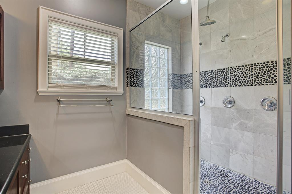 The walk-in shower is large with multiple shower heads and spa style finishes.