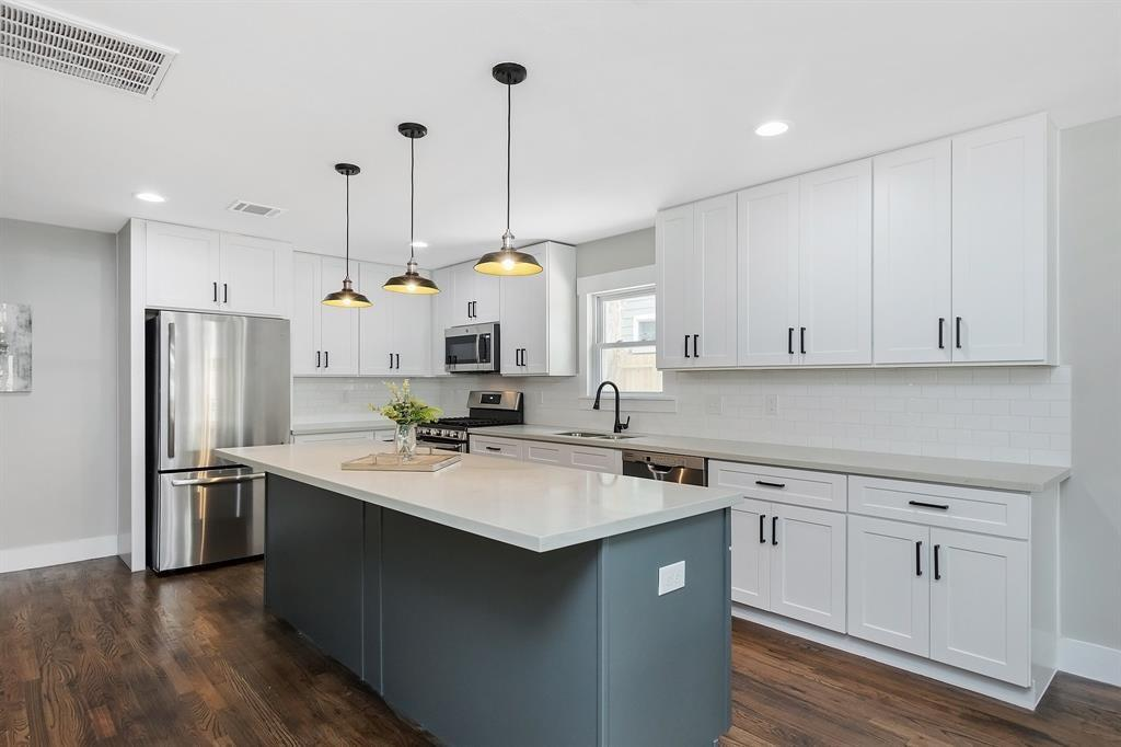 The kitchen is complete with an exceptionally long island with an overhang for seating and pendant lighting.
