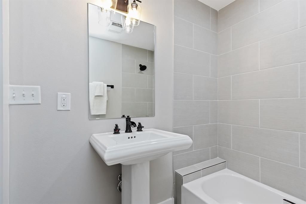 The third full bath with a tub/shower combo is adjacent to the fourth bedroom.