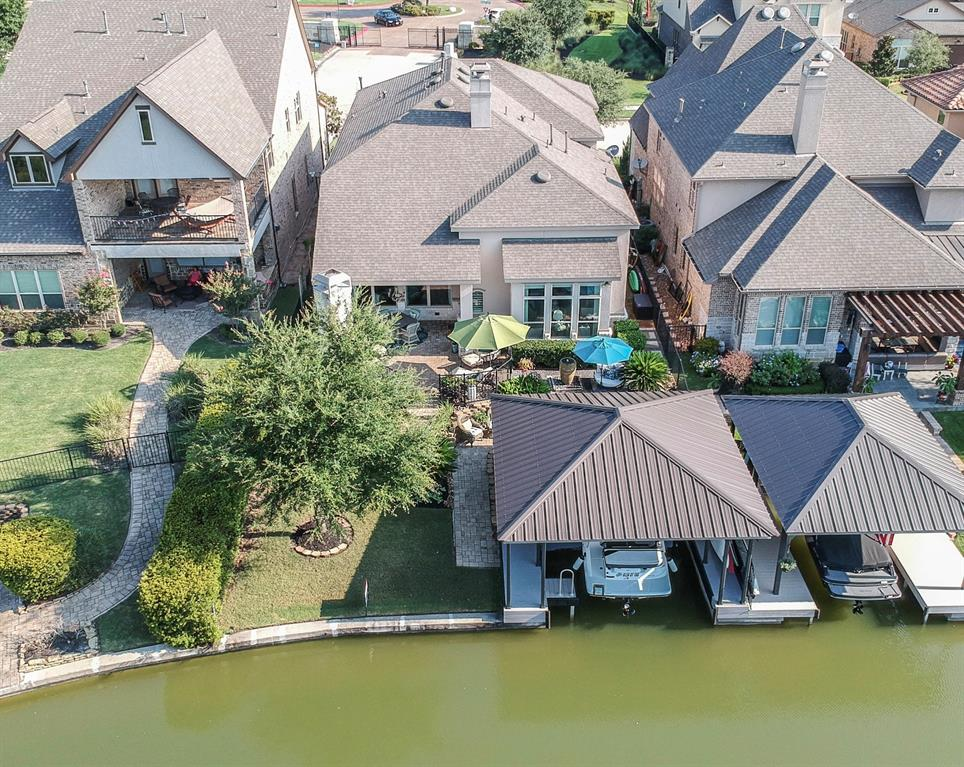 """Magnificent remodeled (former Model) waterfront home in Waterways w/backyard paradise: covered oversized boat house with lift, Trex decking, summer kitchen, outdoor stone fireplace, bubbling fountain lounge area & covered patio. Soaring entry w/custom square wall paneling, Study, Formal Dining & Gourmet Kitchen w/large upgraded granite island & designer cabinets.  Exquisite Master Suite w/plush carpet & swoon worthy bathroom as well as Guest Suite downstairs.  Wood """"Piano Steps"""" lead to 2 Bedrooms/Bath w/2 sinks plus Game Room, Media Room w/surround sound & bar w/wine refrigerator.  Fabulous light fixtures throughout, wood-look tile, gaslog fireplace w/mantel in Living Room, crown molding, custom designed paint, accent walls w/custom stencil & Mud room.  Water softener, 2 water heaters, Smart 5 camera alarm, insulated garage with A/C, sprinklers & landscape lighting.  Only 15 homes in this gated """"community"""" that holds canal concerts on the water for residents.  Lake life at its best!"""
