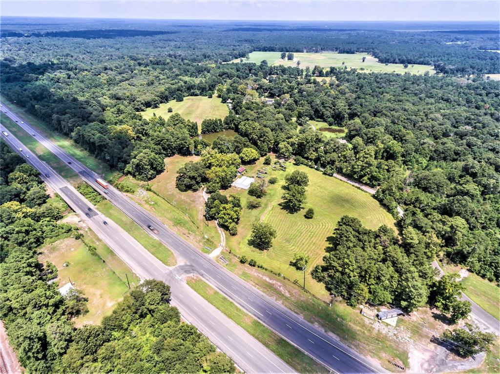 """""""GREAT BUY"""" on this INCREDIBLE """"53 ACRE"""" tract that offers the Best of All Worlds!! This Beautiful Commercial/Residential/Multi Use/Ag Exempt property offers over 2200' of Commercial Frontage in sought after HWY 59 North Area.  This """"Amazing"""" Property has Beautiful Hardwood Trees valued at over $200k, 1+ Acre Stocked Lake, A Creek (Big Creek) which runs through West Side of property with access to Trinity River, Public Utilities and 2000 sq.ft. Metal Barn + Pole Barn. Did I also mention... Included is a Wonderful 1500+ sq.ft. 4 bed 2 bath Brick Home with Storm Shelter for Upscale Country Living on 20 Acres of Cleared Land with planted Bermuda mix grass for Hay Production.  Property can be Subdivided to Accommodate Strip Retail Center on HWY 59 Frontage, Residential Development, Vacation Rentals, RV Park, Cattle Ranch, Multi Family Complex, etc. or to Simply Live on and Enjoy as Your Very Own Personal 53 Acre """"Fully Fenced"""" Paradise!!.  The Possibilities are Limitless!!!!"""