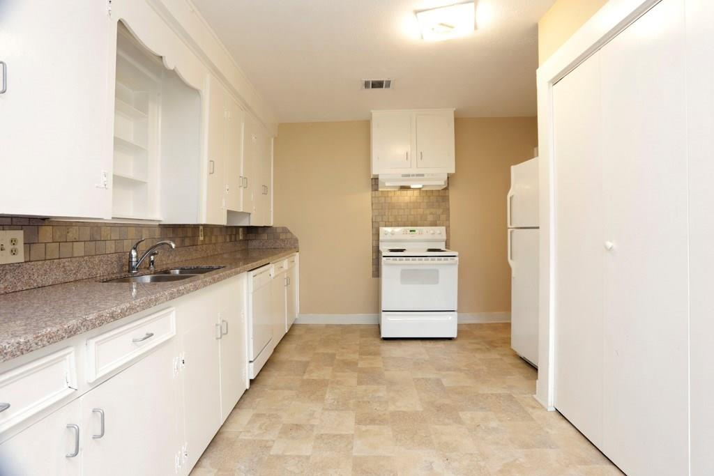 The spacious kitchen has granite counters and an electric range. The doors to the right house the included washer and dryer.