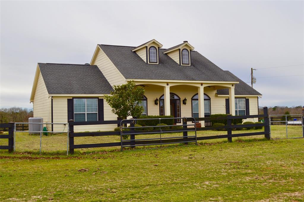 """HORSE RANCH!   This beautiful, custom built three bedroom, two bath home sits off the county road on pretty pasture land. It has a nice entrance, attractive vinyl fencing, and the inviting front porch says, """"WELCOME!"""" This home has soaring ceilings, a fireplace, a large living area, and the kitchen has pretty cabinets, stainless appliances, and attractive counter-tops. The den area upstairs could be a large game room or office. The secluded master suite bath has two vanities, a large walk-in shower, and two walk-in closets. The guest bedrooms share a full bath. The entire home has either wood or tile flooring. Outdoors, there is a nice 40' x 60' shop, large hay barn, pretty rolling terrain, a live creek, and the property is fenced for horses or cattle. Call us today to see this great ranch!"""