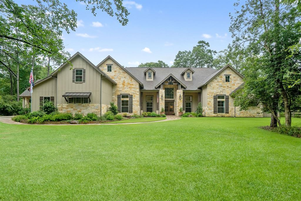 """STUNNING, modern farmhouse style, 1-story custom on nearly 2 acres w/3-car garage + 2-car carport. Great location off 1488 close to shopping. Wdls Schools. Fabulous home w/soaring ceilings, beams, expansive windows, wood floors. Family rm has cathedral ceiling w/beams, dramatic stone FP flanked by dbl doors to lanai w/cathedral ceiling. Jaw-dropping kitchen has oversized island w/room for seating; Custom cabinets go perfectly w/white/gray counters; SS appliances include 48"""" range w/6 burners + griddle, double ovens & pot-filler + warming drwr; W/I pantry has butler pantry & 2nd fridge; B/I desk. Dining has room for large farmhouse table w/open frame bronze lanterns + wine bar w/fridge. Media/game w/sliding barn doors. Master suite has wood flrs, cathedral clgs & dreamy master bath w/free-standing tub flanked by dbl openings to his & her W/I shower. Master closet decked out w/access to laundry rm. Fabulous mud & huge laundry rm. Huge home gym. Amazing art studio. 5 bedrooms & 5.5 baths."""