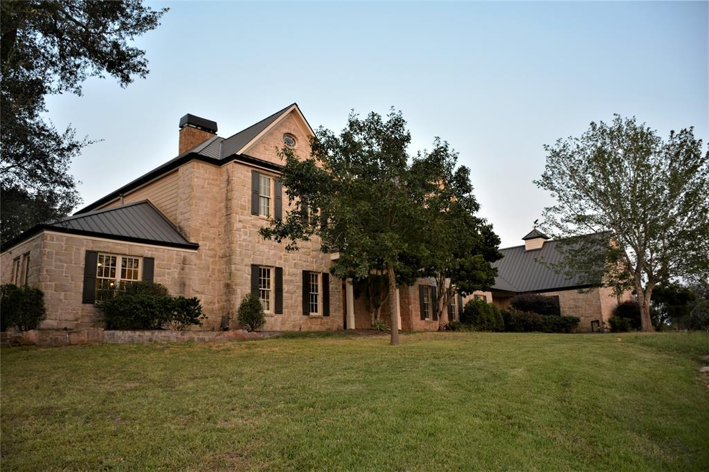 Fabulous custom stone estate high on a hill in Yaupon Creek Estates, a prestigious acreage community covered in century oaks. Down: elegant foyer; amazing liv rm w/stone fp, soaring ceilings; cook's kit; walk-in pantry; formal din rm, informal din w/stone fireplace; butler's pantry & temp control wine rm; media rm; std/library; master suite w/garden bath;  lrg util & 2 half baths.  Up: 3 bed/2 baths, open tv/computer rm w/ext balcony and an int balcony overlooking liv rm.  Features: high ceilings, crown molding, reclaimed pine wood floors, travertine tile, granite counters, large island,  Wolf commercial stove, Sub Zero refrigerator/freezer, built-ins throughout, staircase constructed from antique church pews, aluminum clad doors/windows by Eagle, outdoor stone grill and fire pit, sprinkler and alarm system, standing seam metal roof, Icynene foam insulation, 2-car att gar w/stor rm.  Wildlife exemption. Combo of rolling natural woods & meadows. Conven to Houston, Austin or San Antonio.