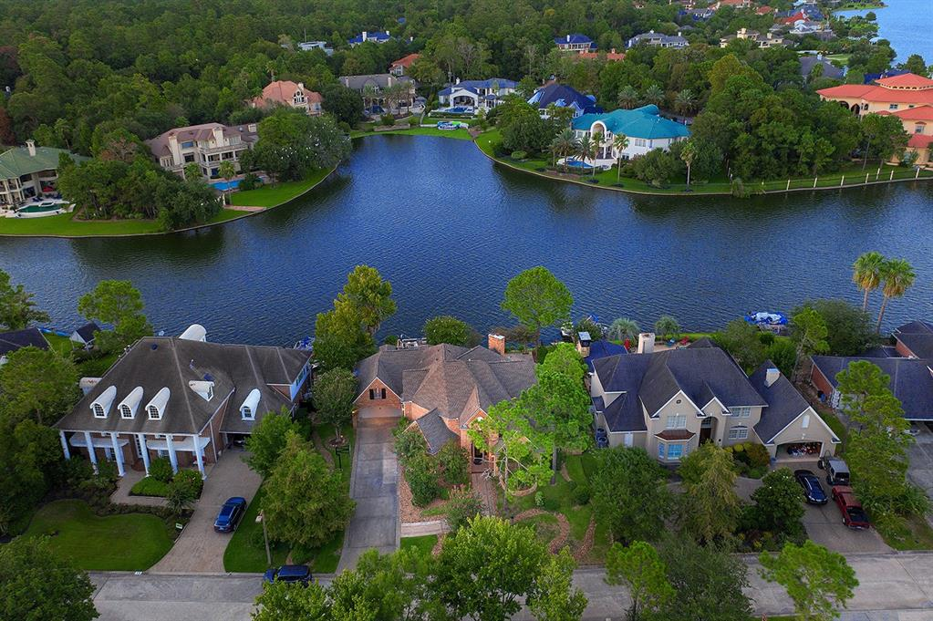 Waterfront custom home overlooking Lake Woodlands with boat dock and pontoon boat! Cruise over to Hughes Landing, dock and enjoy dinner at one of the many restaurants! Centrally located in Panther Creek and close to Northshore Park, Market Street and I-45! Soaring ceilings, gorgeous trim work, built-ins, wraparound balcony, hardwood flooring, abundant storage and large windows provide breathtaking water views throughout the home. Open and bright island kitchen with wine chiller and breakfast bar overlooks the breakfast room and den with gas log fireplace; formal dining and study; master retreat down has French doors that open to the patio and pool; three bedrooms, media and game room up; backyard features sparkling pool with fountains, spa, covered patio, and boat dock!