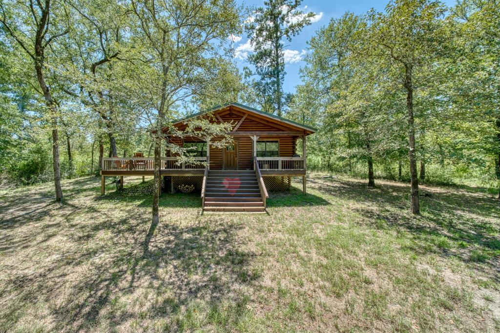 Welcome to Scout's Cabin located in Southern Madison County.  This is truly a dream come true property for those seeking for a secluded, authentic log cabin in the woods.  Built in 2012 (CAD) by Reed Log Homes, this cabin  features 2 bedrooms, 2 full baths, kitchen island, wood burning stove, and impressive outdoor deck.  The 13.5  acre tract is rolling/sloping forested property approximately 15% open, and 85% wooded with mature trees and underbrush with evidence of abundant wildlife.  Black Oak Branch crosses the back of the property and there are several well maintained trails throughout for ATVs and hiking.   Other amenities include partial fencing, a storage shed, implement shed, water well and underground powerlines.  Conveniently located minutes from I-45, the main corridor between Houston to Dallas and approximately 30 minuets to Huntsville.