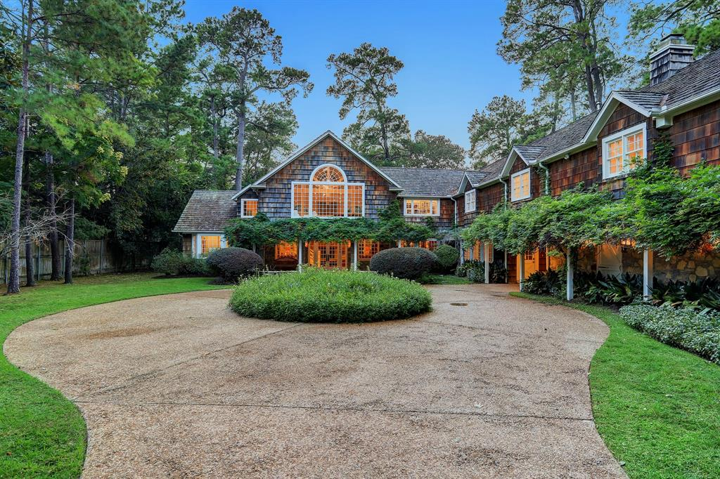 A remarkable wooded retreat encompassing over 2.5 acres in scale with private pond and tennis court nestled in the prestigious Bayou Woods area of close-in Memorial. This enchanting estate was extensively renovated in 2016 offering relaxed refinement with captivating coastal architecture enhanced by the serene and private setting. Inviting Entry opens to an impressive Great Room with double-height cathedral beamed ceiling and adjoining wet bar. Elegant Formal Dining. Gourmet Island Kitchen with informal dining area and access to adjacent Den. Guest Suite down. Primary Suite up with beautiful bath and sizable dressing room. 4 Guest Suites up with Game Room and central Sitting Room/Study. 2 Staircases. Spectacular setting surrounded by towering trees features a private pond with wooden footbridge and clay tennis court with pergola-covered seating space. Circular Motor Court with ample off-street parking and porte-cochere leading to the three-car Garage. VIDEO TOUR IN LINKS.
