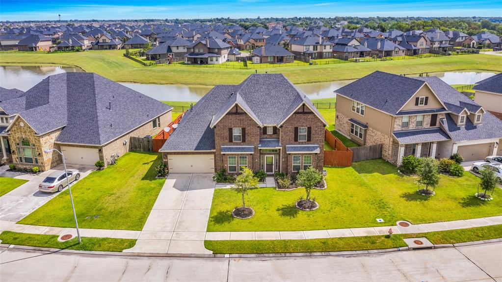 Stunning Large Lake Lot! 3 Car Garage! Energy Star Home! Formal Living & Dining! Grand Entry W/Two Story Wall Of Windows looks out on the Lake! 2 Story Sweeping Iron Stairway! Huge Family Rm W/ High Soaring Ceilings & Corner Fireplace! Large Tile Floors in the Formal Dining, Gourmet Kitchen, Breakfast Rm & Covered Patio! Gourmet Kitchen W/Beautiful Granite Counters, Tall Cabinets, Under-Mount Sink, Tile Back-splash, Built In Stainless Steel Appliances & Walk In Pantry! Primary Suite W/High Coffered Ceilings, French Doors open to Luxurious Bathrm Suite, His & Her Vanities W/Granite Counters, Deep Corner Whirlpool Tub, Huge Walk in Shower, His & Her Walk In Closets! Upstairs discover Guest Suite Tucked away with its Private Bathrm! Also 2 Guest Bedrm W/Hollywood Bathrm, Huge Media & Game Rm! Clubhouse W/Pool, Splash Pad, Gym, Movie Theater, Soccer Field, Volleyball Court, Basketball Court, Covered Playground, & Swings! No Flooding during storms! Outstanding Schools!