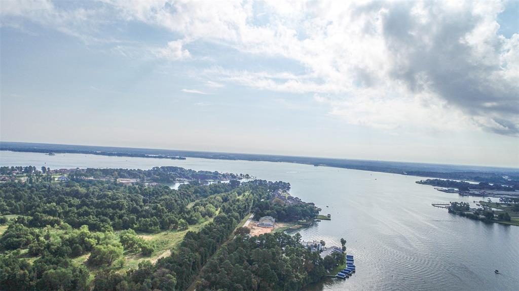 FEEL LIKE YOU ARE ON VACATION EVERY DAY! This waterfront condo has a wonderful view and is right in the heart of the action on Lake Conroe! You are within minutes of Margeritaville and the bulk of the lakefront shopping, dining, boat rentals and more. It's a prime location due to it's waterfront, proximity to everything, and also it's closeness to I45, The Woodlands, Conroe, IAH, and Houston if you want to go into town for a night out.  This complex also has an ELEVATOR so if you want to avoid stairs this one level condo on the 2nd floor works! Take the ELEVATOR up to your 2nd story condo for a better bird's eye view of the lake! Inside you have an updated condo with new lighting, flooring, countertops, paint, and more. This unit looks great. The complex is gated, and has a lot of green space to play which is a nice change from other options on the market. There is a pretty community pool overlooking the lake and place to tie up your boat for the day as well! Come get it quick!